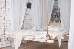 L'interno bianco del sottotetto con il letto d'attaccatura ha sospeso dal soffitto Fotografie Stock Libere da Diritti