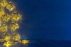 L'interno in bianco di Natale con incandescenza accende le stelle gialle sul fondo di legno del blu di indaco Fotografia Stock