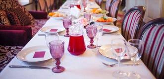 L'interno del ristorante, grande tavola ha posto per il banchetto, decorato in Borgogna tonifica Fotografia Stock