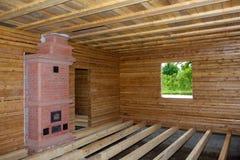 L'interno della casa in legno con il forno ed il pavimento ostacola in costruzione Immagine Stock Libera da Diritti
