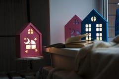 L'interno della stanza del ` s dei bambini, luci notturne accoglienti sotto forma di case sull'incandescenza della finestra ingia fotografia stock