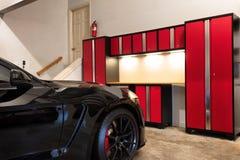 L'interno domestico del garage altamente ha organizzato e pulito con l'automobile parcheggiata fotografia stock