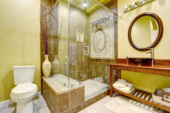 L'interno moderno del bagno con la doccia di vetro della porta e la nave affondano Immagine Stock