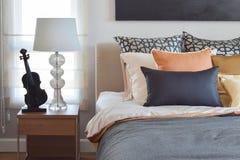 L'interno moderno della camera da letto con l'arancia e l'oro appoggia sul letto e sulla lampada da tavolo Fotografia Stock Libera da Diritti