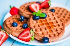 L'intero grano waffles con le bacche su fondo di legno blu Immagini Stock Libere da Diritti