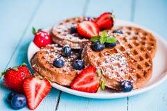 L'intero grano waffles con le bacche su fondo di legno blu Fotografia Stock