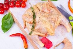 L'intero pollo crudo fresco ha preparato per l'arrosto con la ciliegia del timo, del basilico e dei pomodori immagine stock