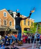 L'interprète de rue monte l'unicyce sur le fil tout en jonglant des baguettes magiques du feu images libres de droits