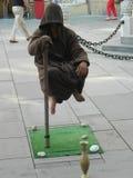 L'interprète de rue reste dans l'entre le ciel et la terre accrochant seulement à un petit poteau Photos stock