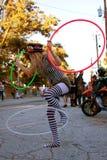 L'interprète féminin de rue amuse avec trois cercles de danse polynésienne Photos stock