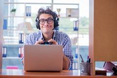 L'intoxiqué de gamer jouant des jeux d'ordinateur à la maison photographie stock
