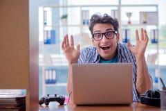 L'intoxiqué de gamer jouant des jeux d'ordinateur à la maison photo stock
