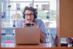 L'intoxiqué de gamer jouant des jeux d'ordinateur à la maison photos stock