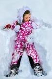 L'inverno d'uso della ragazza del bambino copre la menzogne di neve Fotografia Stock Libera da Diritti