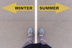 L'inverno e l'estate mandano un sms alle frecce sulla terra, sui piedi e sulle scarpe dell'asfalto Fotografia Stock