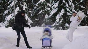 L'inverno nella famiglia della foresta passa il loro tempo libero Finchè il bambino respira l'aria fresca in una sedia a rotelle, video d archivio