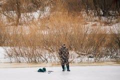 L'inverno tardo di Fisher On Frozen River At La pesca sul ghiaccio dell'inverno è hobby popolare fra gli uomini di bielorussi fotografie stock libere da diritti
