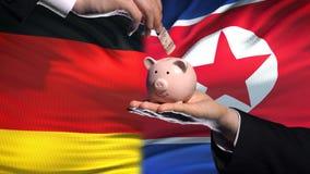 L'investissement de l'Allemagne en Corée du Nord, main met l'argent dans la tirelire, fond de drapeau clips vidéos