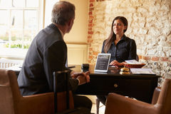 L'invité parlant à la femme à l'hôtel signent le bureau Photographie stock libre de droits