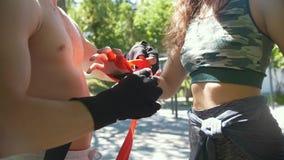 L'involucro maschio del pugile la sua giovane donna delle mani lo aiuta, l'allenamento nel parco - rallentatore video d archivio