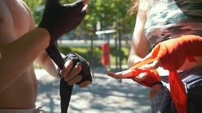 L'involucro maschio del pugile la sua giovane donna delle mani lo aiuta, l'allenamento nel parco - rallentatore archivi video