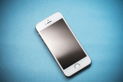 L'iPhone 5s d'Apple d'or sur le fond de papier bleu Images libres de droits