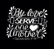 L'iscrizione della mano con il verso della bibbia tramite il servire uno un altro di amore ha fatto su fondo nero Immagini Stock