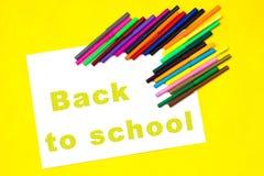 L'iscrizione - di nuovo alla scuola, su uno strato di Libro Bianco circondato dalle matite colorate, indicatori, pitture su una p Fotografia Stock Libera da Diritti