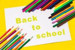 L'iscrizione - di nuovo alla scuola, su uno strato di Libro Bianco circondato dalle matite colorate, indicatori, pitture su una p Immagini Stock