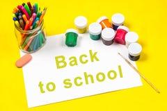 L'iscrizione - di nuovo alla scuola, su uno strato di Libro Bianco circondato dalle matite colorate, indicatori, pitture su una p Immagine Stock Libera da Diritti