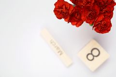 L'iscrizione l'8 marzo con i fiori rossi su un fondo bianco Immagini Stock