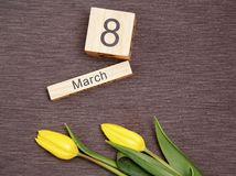 L'iscrizione l'8 marzo con i fiori su un fondo grigio Fotografie Stock