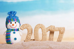 L'iscrizione 2017 nella sabbia e nel pupazzo di neve sui precedenti del mare Fotografie Stock