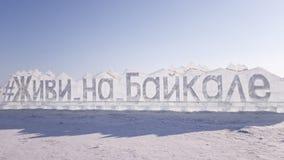 """L'iscrizione sul ghiaccio del lago Baikal congelato dai grandi blocchi di ghiaccio Testo in russo - """"viva su Baikal """" immagini stock libere da diritti"""