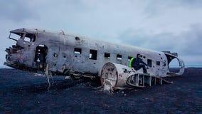 L'Islanda - giovane che si siede su un aeroplano caduto fotografia stock libera da diritti