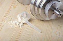 L'isolato della proteina della tazza si trova su superficie di legno vicino alla testa di legno Fotografie Stock Libere da Diritti