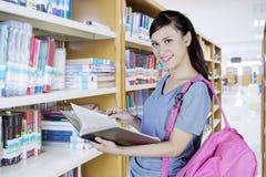 L'istituto universitario grazioso studen leggendo un libro alla biblioteca Fotografia Stock