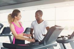 L'istruttore di forma fisica aiuta la giovane donna sulla pedana mobile Immagini Stock