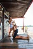 L'istruttore di forma fisica della donna che assiste la giovane donna nell'esercizio si batte Immagini Stock