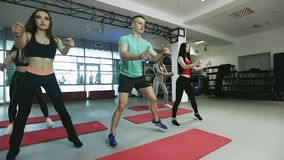 L'istruttore di forma fisica sta lavorando con il gruppo di giovani donne nella palestra di forma fisica stock footage