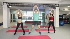 L'istruttore di forma fisica sta lavorando con il gruppo di giovani donne nella palestra di forma fisica video d archivio