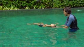 L'istruttore di nuoto dell'uomo insegna al nuoto del ragazzino nello stagno archivi video