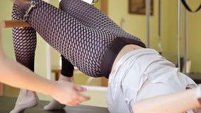 L'istruttore di Pilates aiuta il cliente a esercitarsi di forma fisica sul trapezio, nella palestra nella stanza archivi video