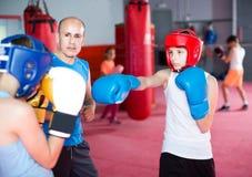 L'istruttore di pugilato segue molto attentamente gli adolescenti in pugilato d'allenamento Fotografia Stock Libera da Diritti