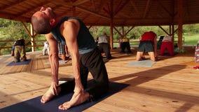 L'istruttore di yoga conduce un seminario che esegue un asana che allunga i muscoli dell'addome video d archivio