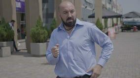 L'istruttore divertente vigoroso di ballo che mostra la salsa fa un passo eseguendo sulle vie urbane nella città - archivi video