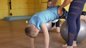 L'istruttore Helping Boy Doing si esercita sulla palla adatta stock footage