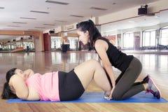 L'istruttore la donna grassa che di aiuti per fare si siede aumenta Immagine Stock