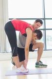 L'istruttore maschio che assiste la donna con l'allungamento si esercita nello studio di forma fisica Immagine Stock