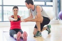 L'istruttore maschio che assiste la donna con pilate si esercita nello studio di forma fisica Immagine Stock Libera da Diritti